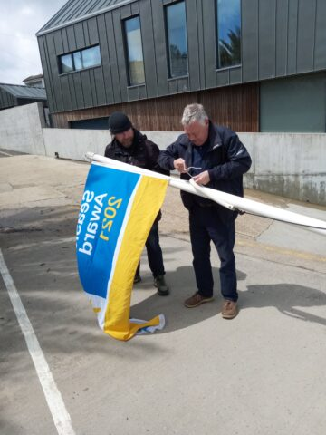 Chairman and Clerk attaching flag to flagpole