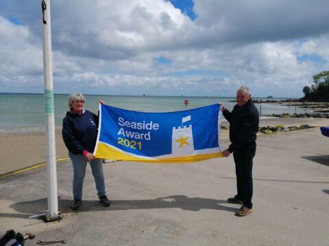 Cllrs Elliott & Hardie holding up a Beach Award flag